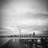 Monochrome city of Seattle across Elliott Bay from West Seattle along fishing pier