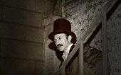 monochrome evil victorian man  with top hat in cellar