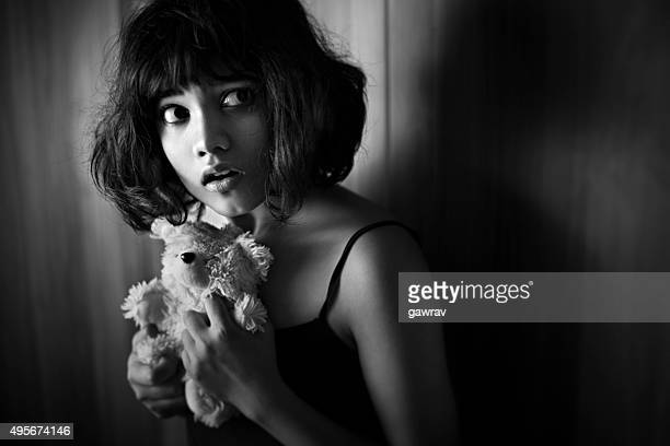 Monochrome image of frightened Asian girl with her teddy bear.