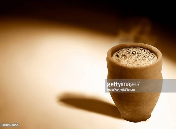Monochrome image of hot steaming chai in traditional cup made of mud