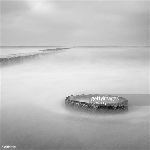 Monochrome long exposure photo of an old tire on the shore