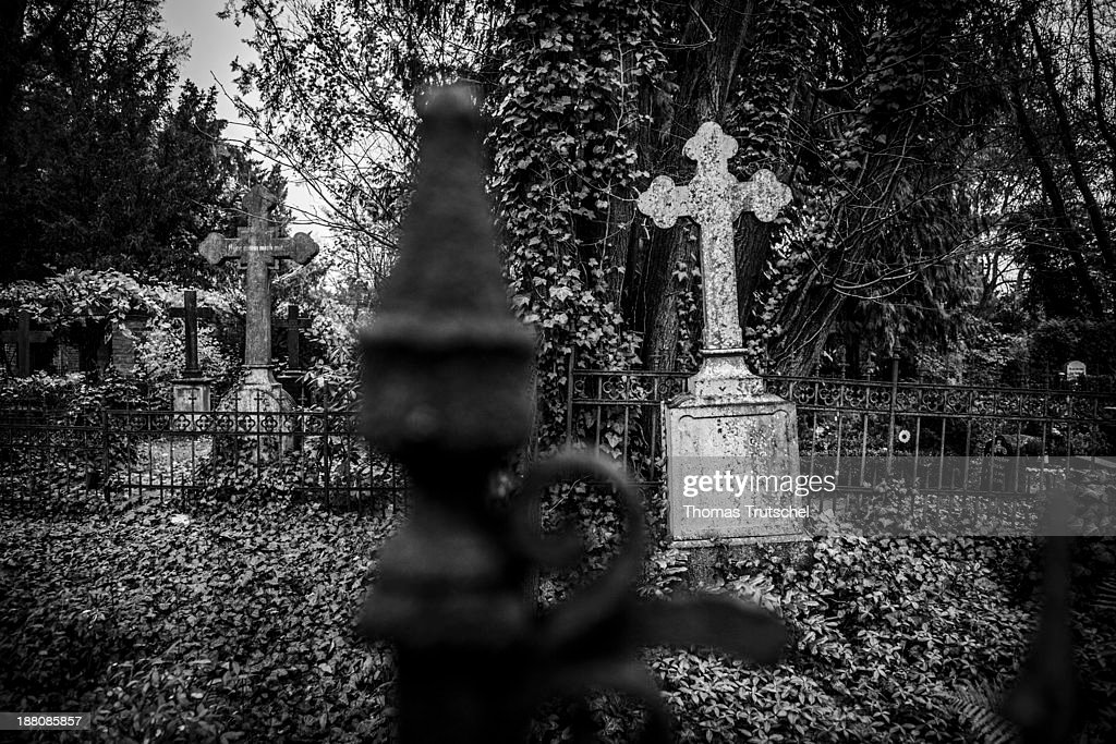 Monochrome picture of an old and weathered gravesite on a graveyard, on November 7, 2013, in Berlin, Germany. Stony cross on a cemetery.