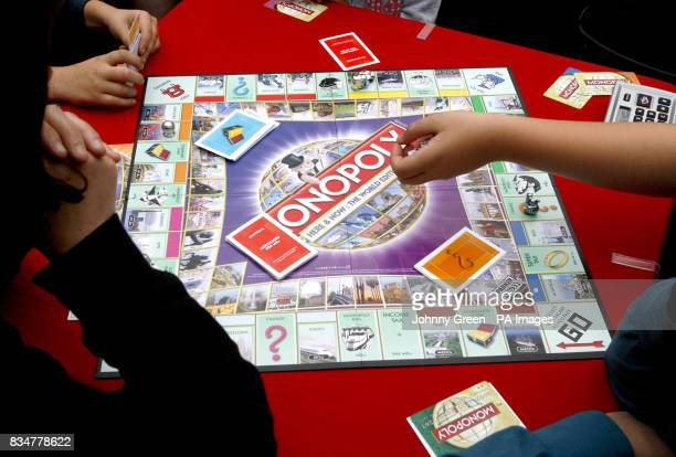 Monopoly enthusiasts play the firstever international Monopoly edition game board at Covent Garden Piazza in central London as they take part in a...