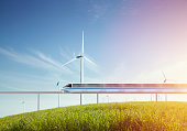 Monorail and wind turbines in grassy field