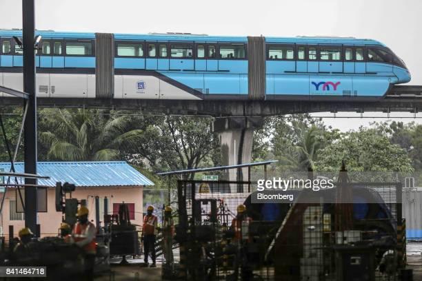 A monorail train operated by Mumbai Metropolitan Region Development Authority travels along an overhead track past the Mumbai Metro Rail Corp casting...