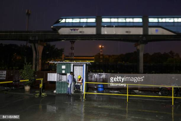A monorail train operated by Mumbai Metropolitan Region Development Authority travels along an overhead track past an entrance to the Mumbai Metro...