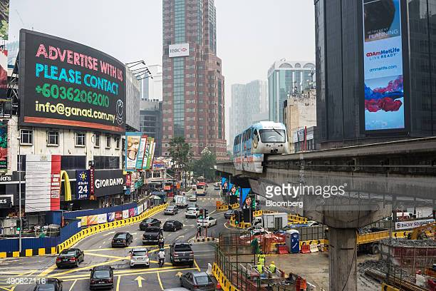 Monorail train operated by Rapid Rail Sdn Bhd travels along an elevated track as traffic passes a digital billboard in the Bukit Bintang area of...