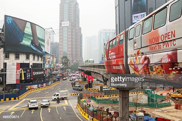 Monorail train operated by Rapid Rail Sdn Bhd travels along an elevated track as buildings in the background stand shrouded in haze in the Bukit...