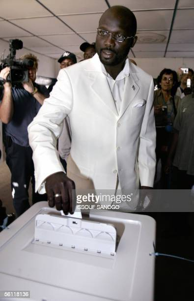 Liberian hero star and presidential candidate George Weah casts his vote 08 November 2005 at a polling station in Monrovia Liberians voted today to...