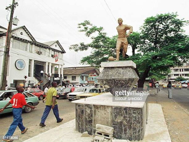 Monrovian pedestrians on Broad Street look up at a newlyerected statue of Liberia's most famous son AC Milan's striker George Weah 18 July a day...