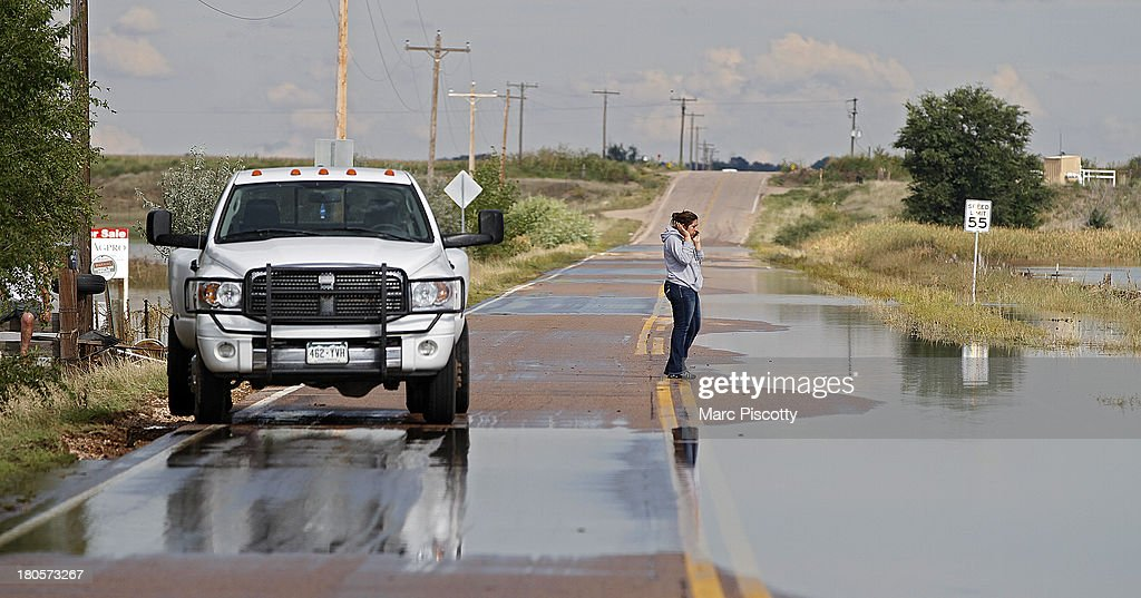 Monse Sanchez, 19, talks on her phone in front of her flooded home and property on September 14, 2013 in La Salle, Colorado. The Sanchez family has lived there for 11 years and said they've never seen anything even close to this level of flooding in the area. Heavy rains for the better part of week fueled widespread flooding in numerous Colorado towns. The historic flooding forced thousands to evacuate the area and more rain is predicted through the weekend.