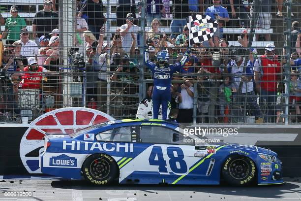 Monster Energy NASCAR Cup Series driver Jimmie Johnson celebrates with the checkered flag after winning of the Monster Energy NASCAR Cup Series...