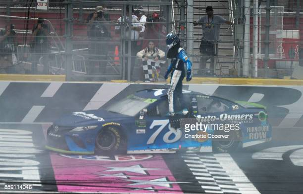 Monster Energy NASCAR Cup Series driver Martin Truex Jr gets out of he is car at the finish line to claim the checkered flag after winning the Bank...
