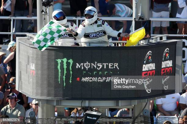 Monster Energy NASCAR Cup Series official waves a green and white checkered flag to end a segment during the 59th Annual DAYTONA 500 at Daytona...