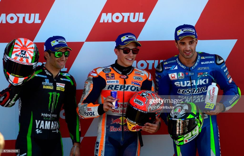 Monster Yamaha Tech 3 French rider Johann Zarco (L), Repsol Honda Team's Spanish rider Marc Marquez (C) and Team Suzuki Ecstar's Italian rider Andrea Iannone (R) celebrate after the second MotoGP qualifying session of the Valencia Grand Prix at Ricardo Tormo racetrack in Cheste, near Valencia on November 11, 2017. Repsol Honda Team's Spanish rider Marc Marquez took the pole position. /