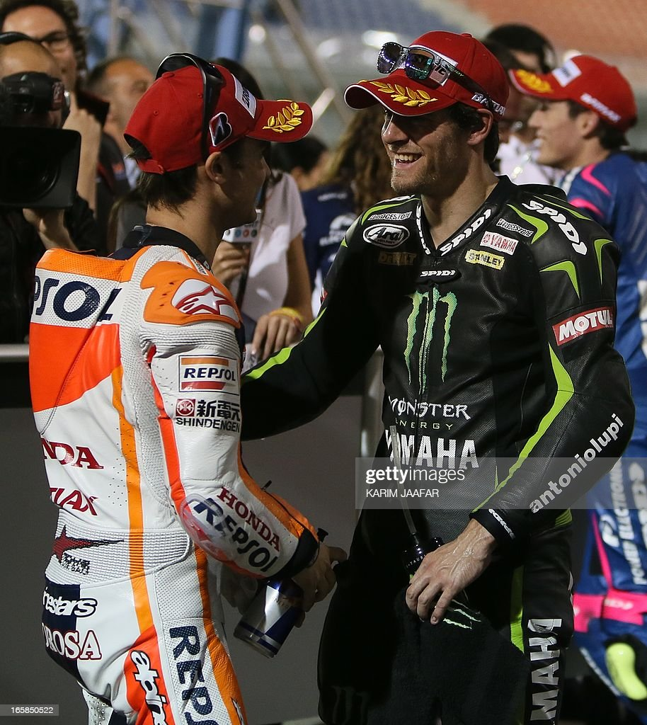 Monster Yamaha Tech 3 MotoGP rider Cal Crutchlow (R) of Great Britain celebrates with Repsol Honda MotoGP rider Dani Pedrosa (L) of Spain after a qualifying practice session part of the Qatar Grand Prix on April 6, 2013 at the Losail International Circuit in the Qatari capital Doha.