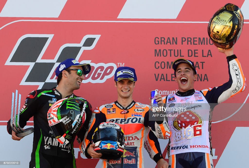 Monster Yamaha Tech 3's French rider Johann Zarco, Repsol Honda Team's Spanish rider Dani Pedrosa and Repsol Honda Team's Spanish rider Marc Marquez celebrate on the podium of the MotoGP race of the Valencia Grand Prix at Ricardo Tormo racetrack in Cheste, near Valencia on November 12, 2017. Spain's Marc Marquez sealed his sixth world championship and fourth in the premier MotoGP category with third place at the Valencia Grand Prix. Marquez's Honda teammate Dani Pedrosa won the race from France's Johann Zarco in second. MARCOU