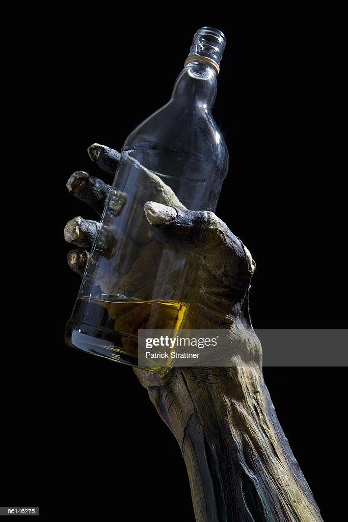 Monster's hand holding a bottle