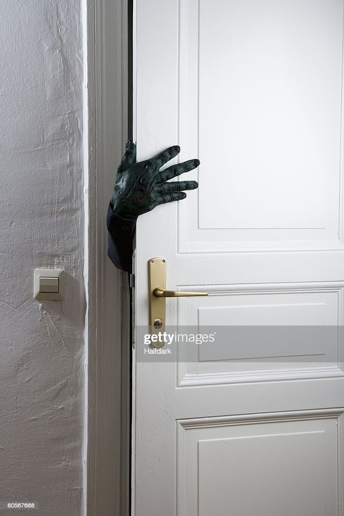 A monster's hand reaching from a behind a door