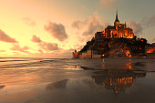The buildings and the abbey of Mont Saint Michel are lit at sunset on a summer evening. Reflections of this famous island in Normandy, France, can be seen in the low tide water at the bay.