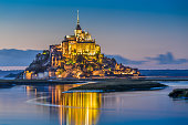 Beautiful view of famous Le Mont Saint-Michel tidal island in beautiful twilight during blue hour at dusk, Normandy, northern France.