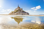 Panoramic view of famous Le Mont Saint-Michel tidal island on a sunny day with blue sky and clouds, Normandy, northern France.