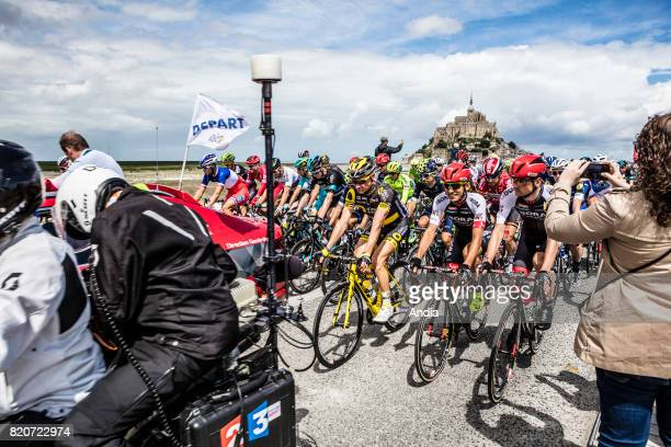 Mont SaintMichel northwestern France on publicity caravan before the start of the 2016 Tour de France bicycle race Cyclists and race director's car...