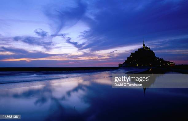 Mont St Michel reflected in the bay at dusk.