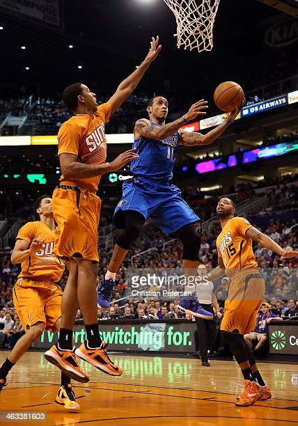 Monta Ellis of the Dallas Mavericks lays up a shot past Channing Frye and Marcus Morris of the Phoenix Suns during the first half of the NBA game at...