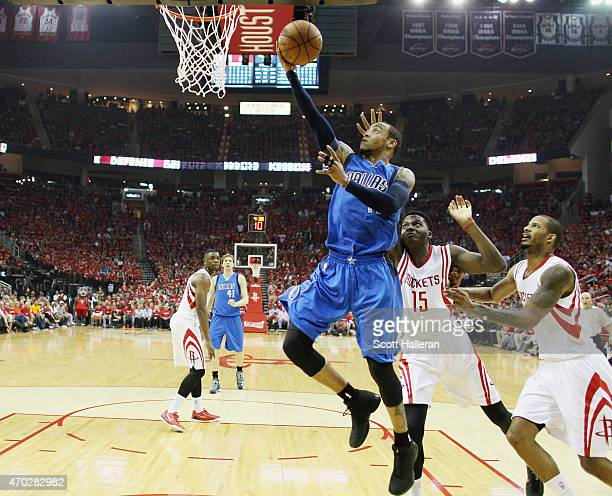 Monta Ellis of the Dallas Mavericks takes a shot over Clint Capela and Trevor Ariza of the Houston Rockets during Game One in the Western Conference...