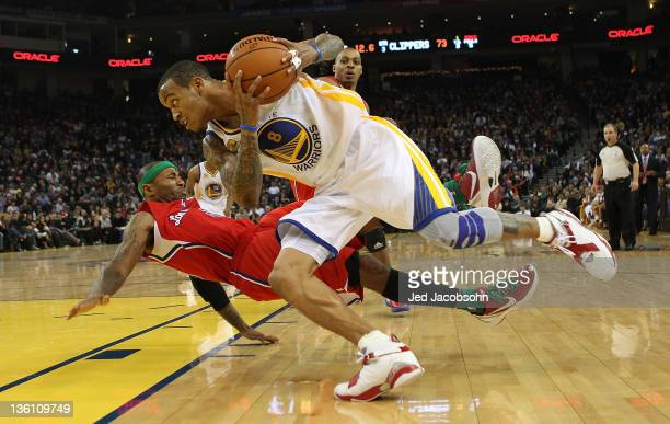 Monta Ellis of the Golden State Warriors drives against Mo Williams of the Los Angeles Clippers during the season opener at Oracle Arena on December...