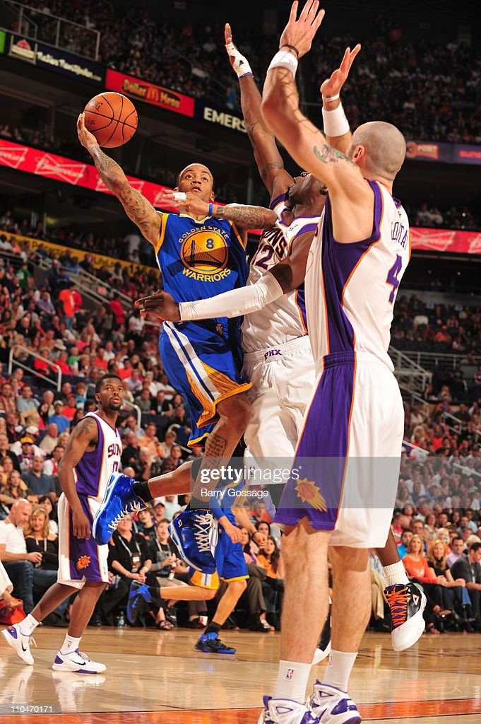 <a gi-track='captionPersonalityLinkClicked' href=/galleries/search?phrase=Monta+Ellis&family=editorial&specificpeople=567403 ng-click='$event.stopPropagation()'>Monta Ellis</a> #8 of the Golden State Warriors drives for a shot against <a gi-track='captionPersonalityLinkClicked' href=/galleries/search?phrase=Mickael+Pietrus&family=editorial&specificpeople=202910 ng-click='$event.stopPropagation()'>Mickael Pietrus</a> #12 and <a gi-track='captionPersonalityLinkClicked' href=/galleries/search?phrase=Marcin+Gortat&family=editorial&specificpeople=589986 ng-click='$event.stopPropagation()'>Marcin Gortat</a> #4 of the Phoenix Suns in an NBA game played on March 18, 2011 at U.S. Airways Center in Phoenix, Arizona.