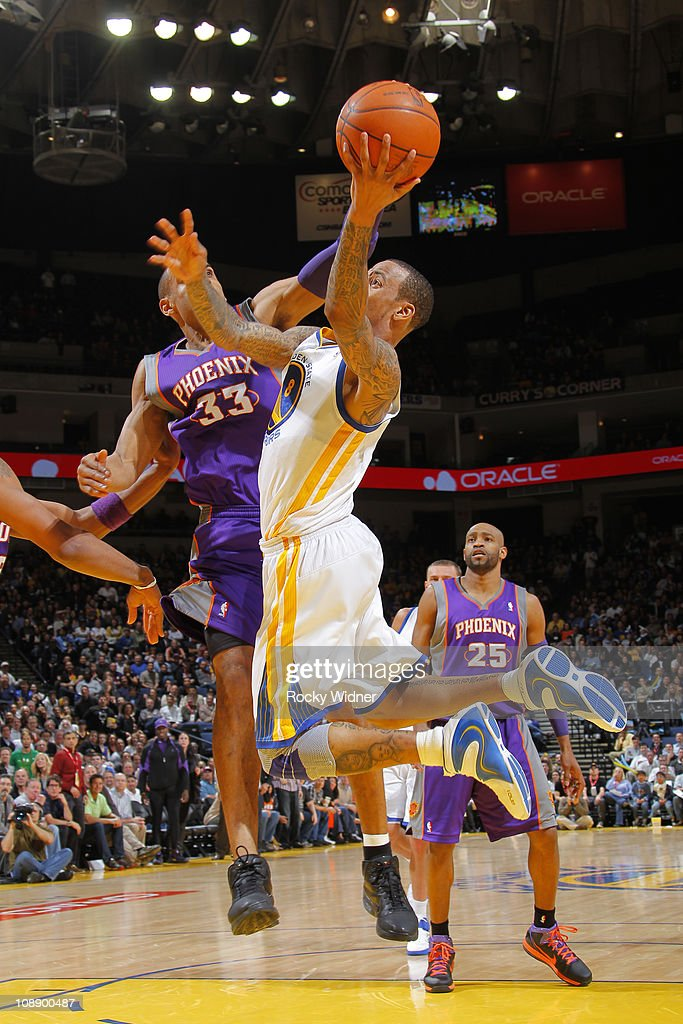 <a gi-track='captionPersonalityLinkClicked' href=/galleries/search?phrase=Monta+Ellis&family=editorial&specificpeople=567403 ng-click='$event.stopPropagation()'>Monta Ellis</a> #8 of the Golden State Warriors flips up a wild shot after making contact with <a gi-track='captionPersonalityLinkClicked' href=/galleries/search?phrase=Grant+Hill+-+Basketball+Player&family=editorial&specificpeople=201658 ng-click='$event.stopPropagation()'>Grant Hill</a> #33 of the Phoenix Suns on February 7, 2011 at Oracle Arena in Oakland, California.