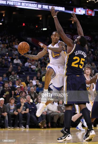 Monta Ellis of the Golden State Warriors looks to pass around Al Jefferson of the Utah Jazz at Oracle Arena on January 7 2012 in Oakland California...