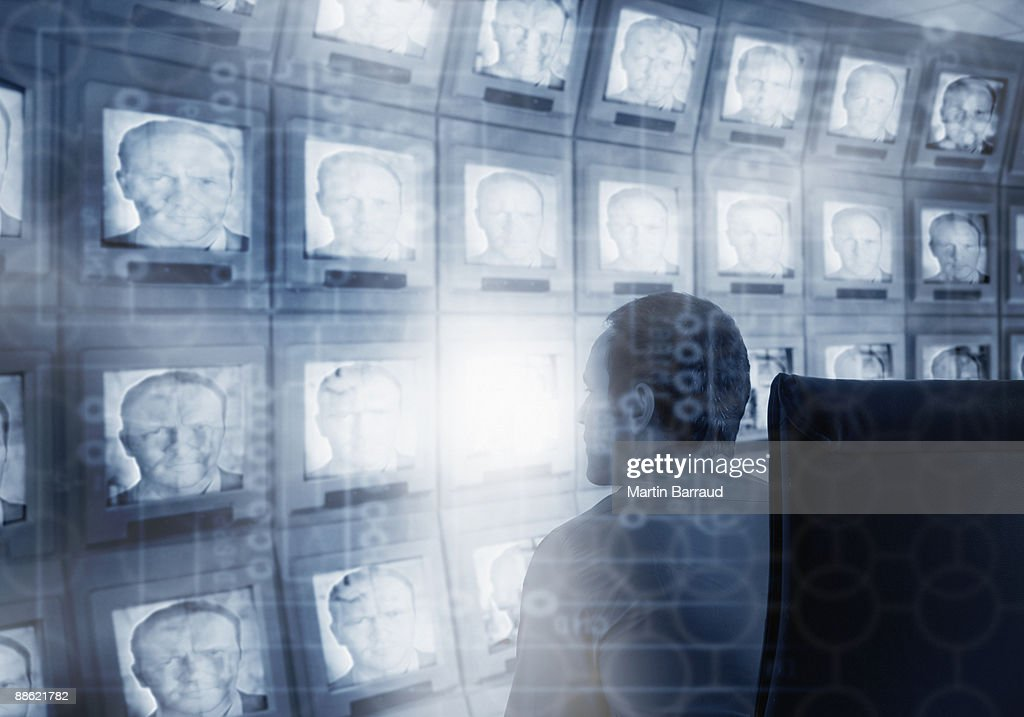 Montage of man, microchip and bank of compute monitors : Stock Photo
