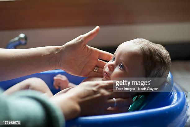 USA, Montana, Baby (2-5 months) bathing in baby bathtub