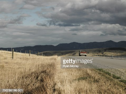USA, Montana, Bozeman, person driving SUV down dirt road, rear view