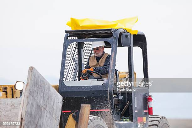 USA, Montana, Kalispell, Senior man working on earthmover