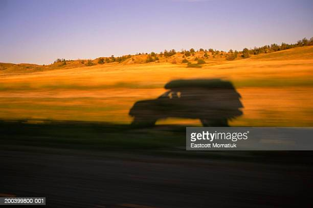 USA, Montana, SUV casting shadow on roadside, sunset (blurred motion)