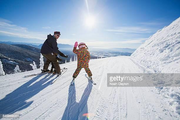 USA, Montana, Whitefish, Father skiing with children (6-7, 8-9)