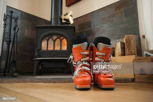 USA, Montana, Whitefish, Ski boots drying in front of fireplace