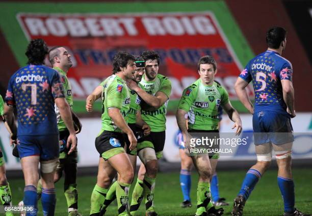 Montauban's fullback Johan Dalla Riva is congratulated by his teammates after scoring a try during the French Top 14 rugby union match Montauban vs...