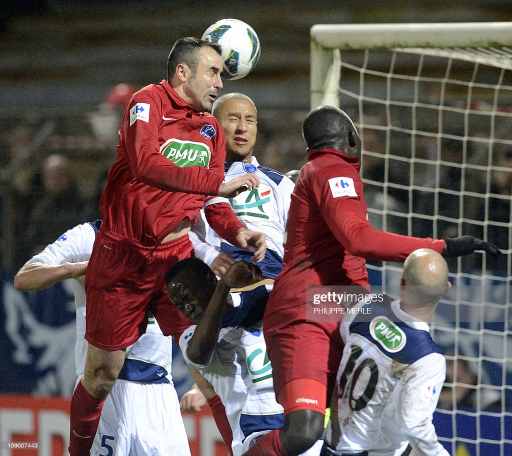 Montceau's French forward Gary Perchet (C) heads the ball during the French Cup football match, Montceau vs Troyes, on January 5, 2013 at the Alouette stadium in Montceau-les-Mines.