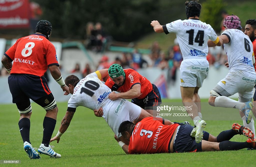 Mont-de-Marsan New-Zealander fly-half Matty James (2L) is tackled by Aurillac Austallian prop Lotu Tokeiaho (down) and by Aurillac Georgian winger Merab Sharikaze (C) during the French Union Pro D2 rugby match Aurillac vs Mont-de-Marsan at the Jean Alric stadium in Aurillac, central France, on May 28, 2016.