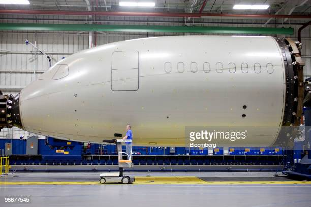 Monte Heincker rides in a lift as he removes positioning targets from a Boeing 787 composite forward fuselage section after window and door openings...