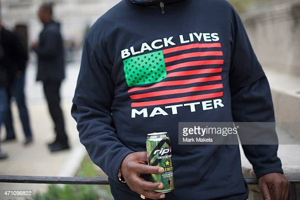 Monte Jackson drinks an energy drink with a newly purchased tshirt stating 'Black Lives Matter' outside City Hall before a protest in honor of...