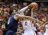 Monte Morris of the Iowa State Cyclones takes a shot as Jaysean Paige of the West Virginia Mountaineers blocks in the first half of play at Hilton...