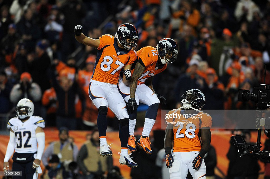 Montee Ball #28 and Eric Decker #87 celebrate with Andre Caldwell #12 of the Denver Broncos after he scored a first quarter touchdown against the San Diego Chargers at Sports Authority Field at Mile High on December 12, 2013 in Denver, Colorado.
