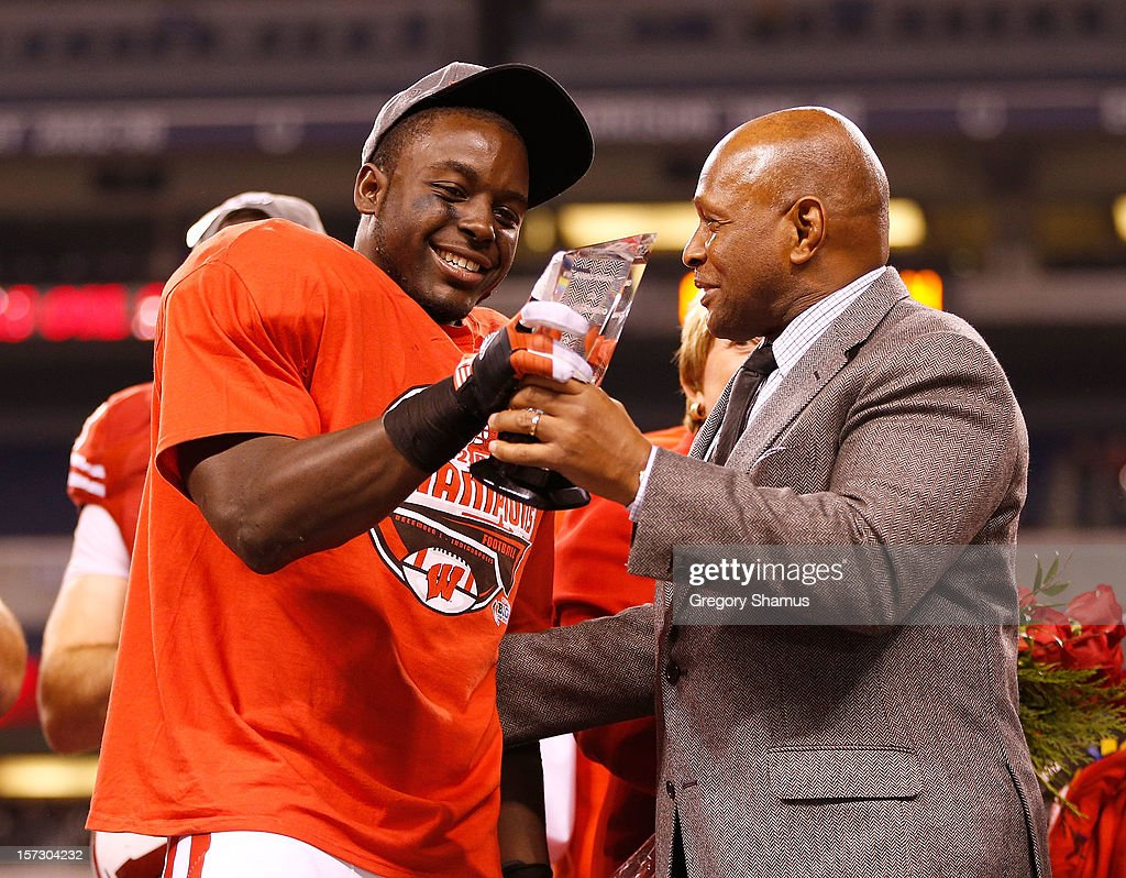 Montee Ball #28 of the Wisconsin Badgers receives the Grange-Griffin Most Valuable Player Award from Archie Griffin after defeating the Nebraska Cornhuskers 70-31in the Big 10 Conference Championship Game at Lucas Oil Stadium on December 1, 2012 in Indianapolis, Indiana.