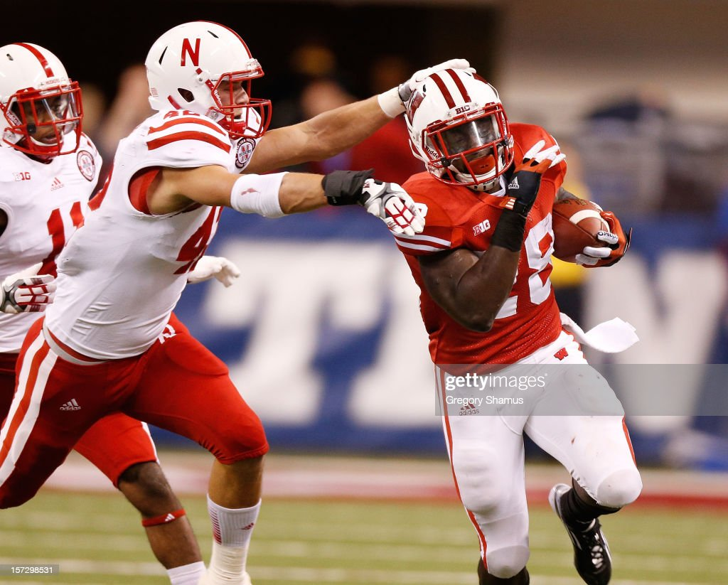 Montee Ball #28 of the Wisconsin Badgers tries to get around the tackle of Sean Fisher #42 of the Nebraska Cornhuskers during a second quarter run during the Big 10 Conference Championship Game at Lucas Oil Stadium on December 1, 2012 in Indianapolis, Indiana.